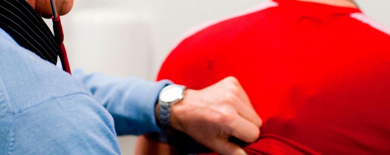 Zorgverlener die met een stethoscoop een cliënt nakijkt